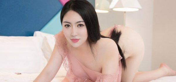 A Korean masseuse knelt on a bed in a pink see through top and up for meeting in London Soho near the Queen's Theatre