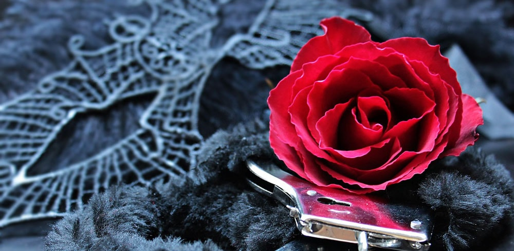 A sexy black massage mask, a red rose and a pair of handcuffs that can be used to spice up a relationship