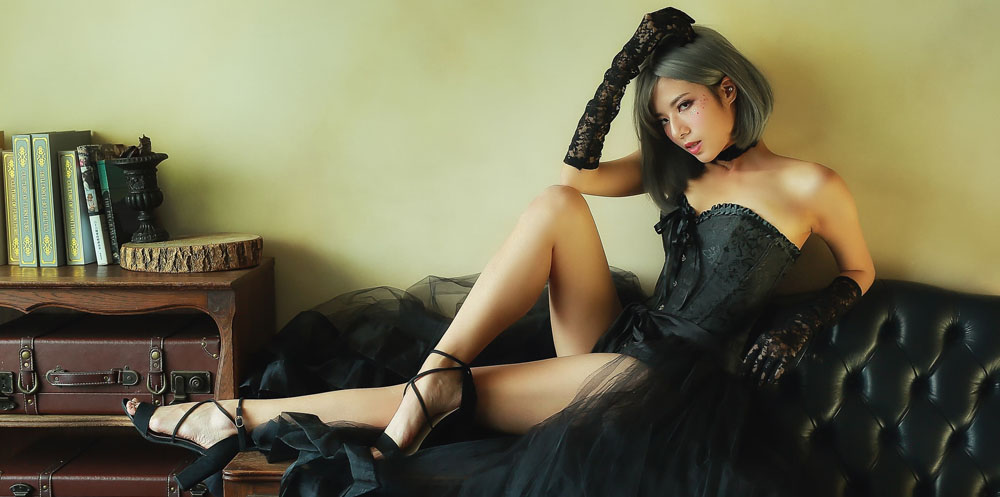 An Asian masseuse lay on a sofa in a sexy black outfit