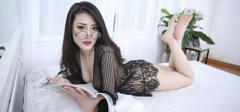 A professional Asian massage therapist lay on a hotel bed in a lace black dress