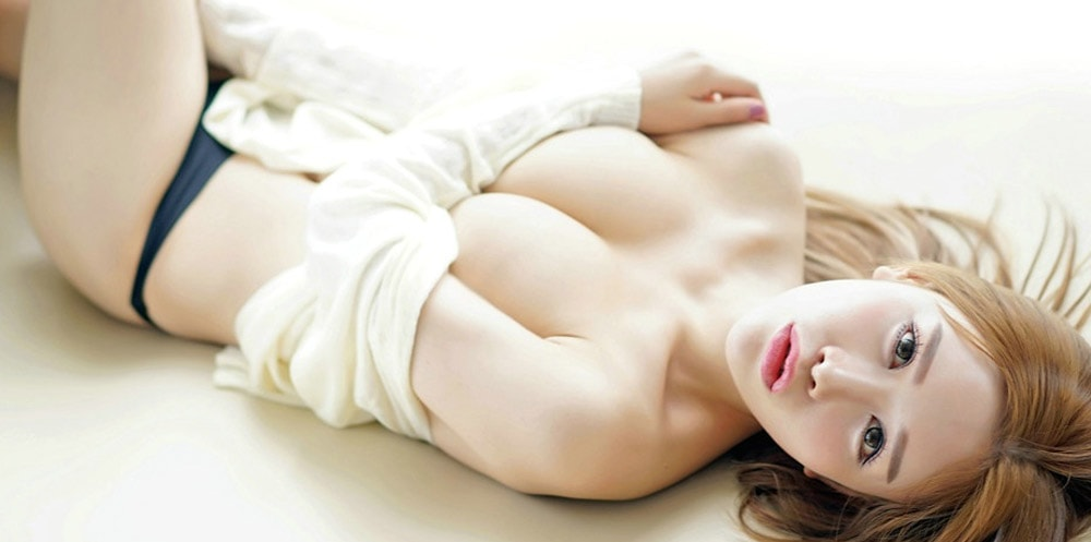 A red headed Asian masseuse lay down topless