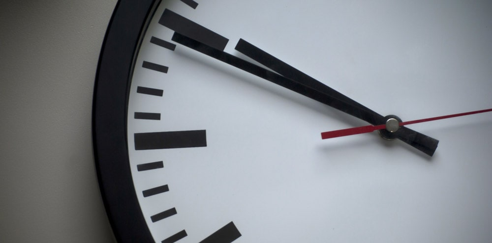 A white analogue clock hanging from a wall