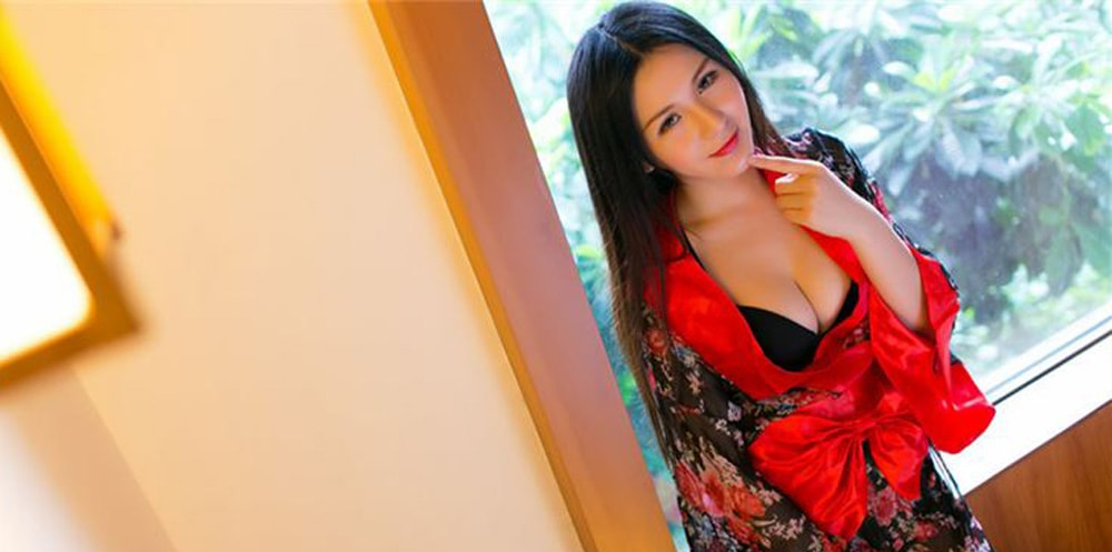 A Chinese masseuse stood up wearing a red flowery dress