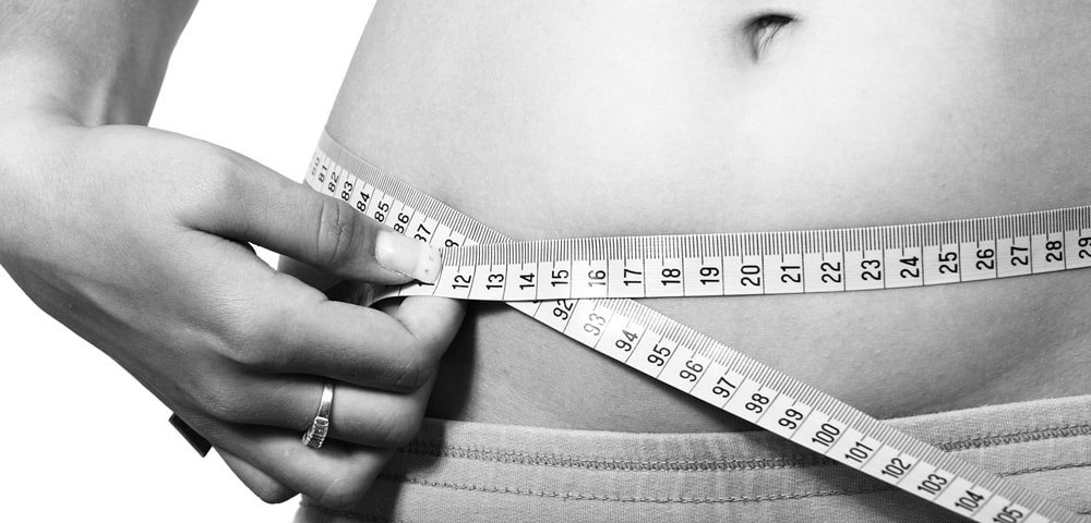 A person measuring their stomach