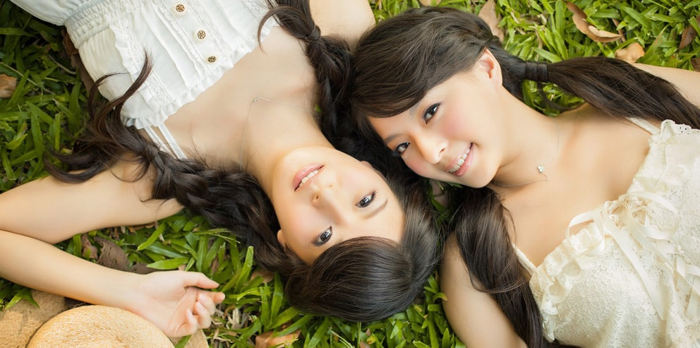 Two Asian massage therapists lay on the floor outside