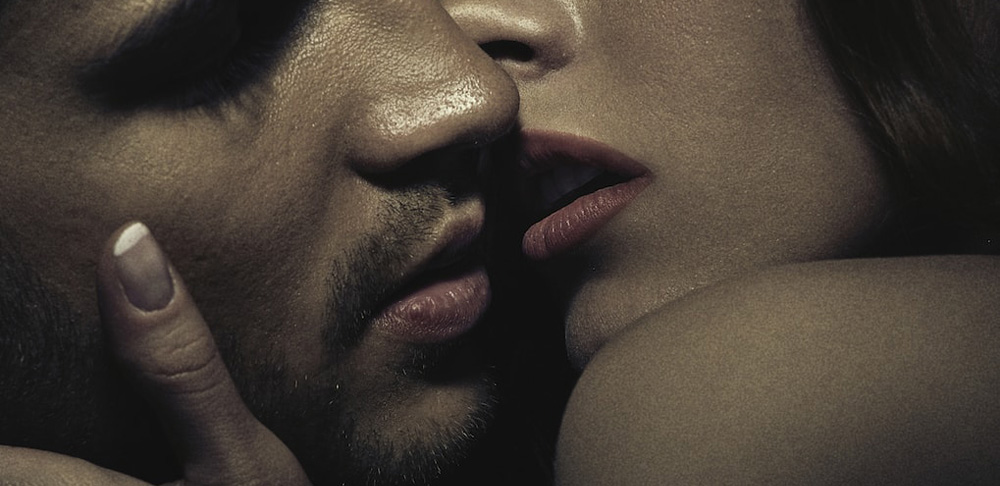 A massage therapist passionately kissing a male client