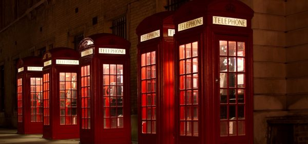 Five red telephone boxes lit up at night. Use one to book a massage in London with an Asian masseuse of your choice